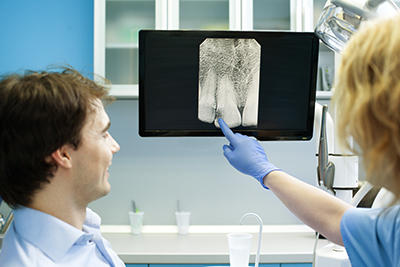 Dentist explaining digital x-ray to patient