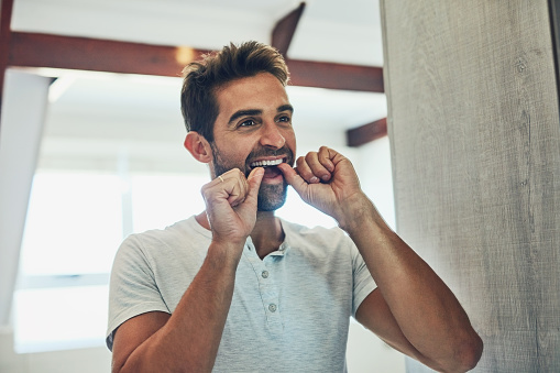Man flossing to prevent gum disease